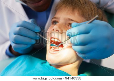 african male dentist examining little boy teeth close up