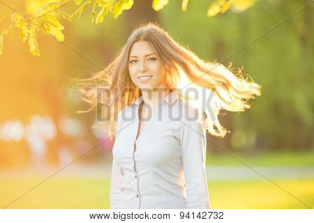 Romantic girl outdoors enjoying nature Beautiful Model in Casual jeans in sun light Long healthy Hair Blowing in Wind Backlit Warm Color Tones Sunshine woman  Sunny Summer Day Autumn Summertime Glow
