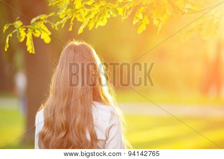 Young woman with long hair turned back  outdoors in sun light Warm Color Tones Beauty Sunshine woman Backlit Sunny Summer Day Autumn Summertime Glow Sun