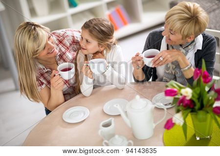 Mom and daughter on a visit to with her grandmother, three generations together drinking tea