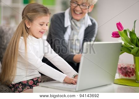 Smiling grandmother watching granddaughter using laptop