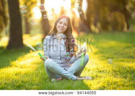 Young fashion casual woman blow bubbles in sunset in park Springtime Summertime Trendy girl sitting on  grass in  sunset Spring landscape background.  Sun rays Summer scene Sunlight background Backlit