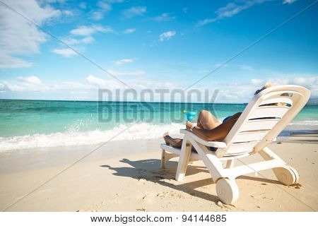 Woman  sitting on a beach chair and holding cocktail on a beach, back view