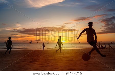 Sunset silhouettes playing beach football kick-ups soccer ball