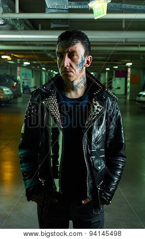 A Man With Tattooed Face In Leather Jacket On Parking
