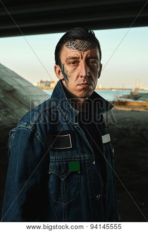 Outdoor Portrait Of Man With Tattooed Face In Denim Jacket