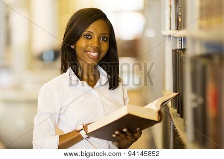 pretty female afro american university student reading book in library