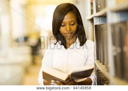 pretty african college girl reading a book in library