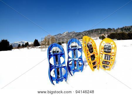 Four Blue And Orange Snowshoes In Mountains