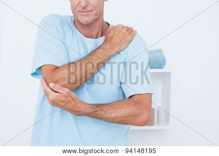 Man suffering from elbow pain in medical office