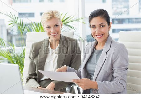 Businesswomen looking at camera and reading files in an office