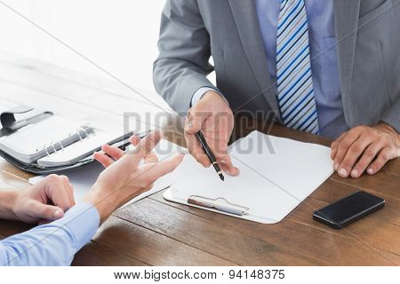 Businessman explaining contract to co worker in an office