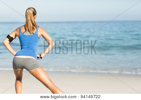 Wear view of fit woman stretching her leg at the beach