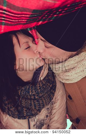 Winter kiss, outdoor portrait of young pair, in the winter forest