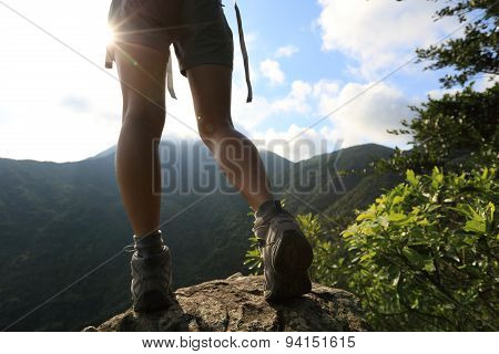 young woman hiker legs on mountain peak rock