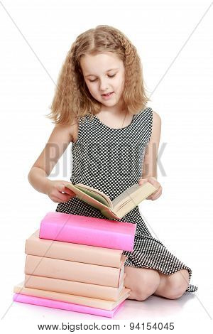 The school age girl reading a book