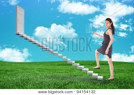Businesswoman stepping up against green field under blue sky