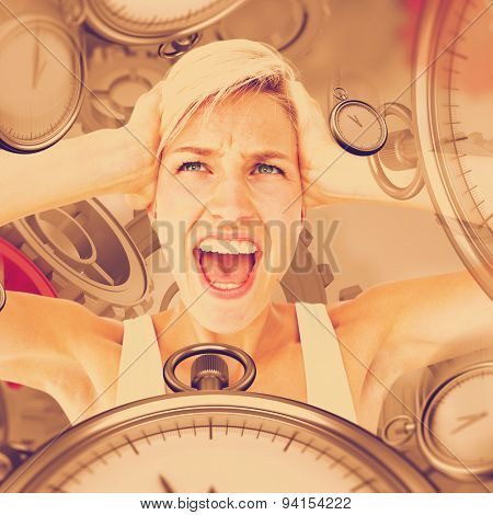 Angry blonde screaming and holding her head against grey vignette