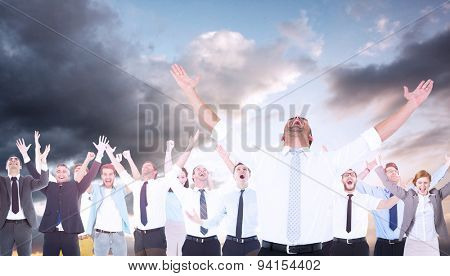 Handsome businessman cheering with arms up against blue and orange sky with clouds