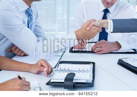 Business colleagues shaking hands in the office