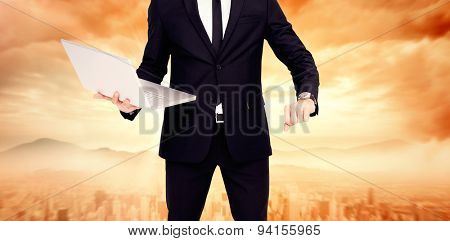 Focused businessman in suit holding laptop against sun shining over city