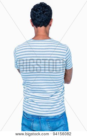 Rear view of man with arms crossed on white background