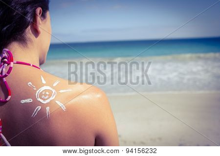 Brunette with sun tan lotion on her shoulder at the beach