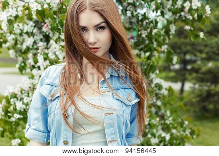 beautiful sexy cute sweet girl with long red hair and green eyes in a denim jacket near a flowering