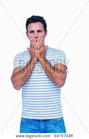 Sad man with his hands on his mouth on white background