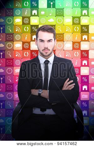 Serious businessman sitting with arms crossed against app wall
