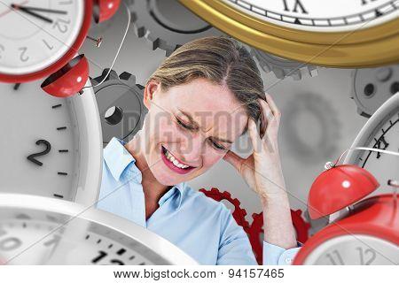 Businesswoman with headache against grey vignette
