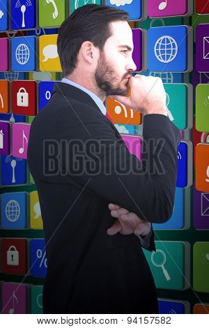 Thinking businessman standing with hand on chin against green background with vignette