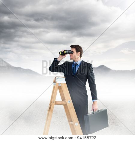 Businessman looking on a ladder against blue sky