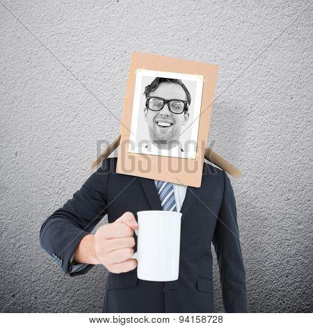 Businessman with photo box on head against grey wall