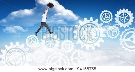 Businessman leaping with his briefcase against bright blue sky with clouds
