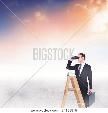 Businessman looking on a ladder against blue and orange sky