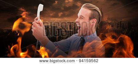 Businessman shouting at phone against stormy sky over city