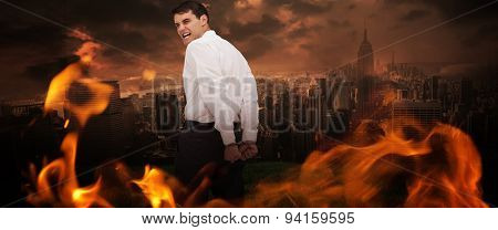 Rear view of young businessman wearing handcuffs against stormy sky over city