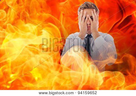 Businessman with a headache against fire