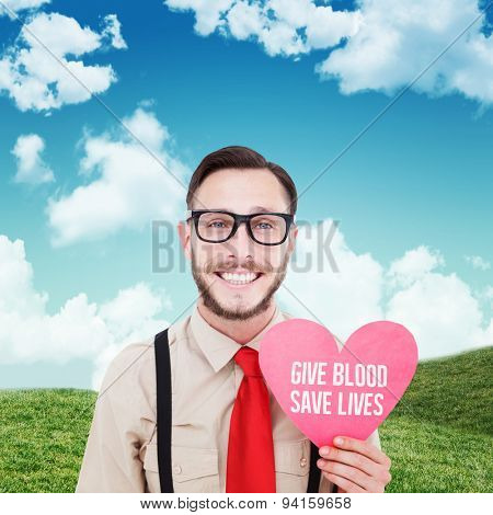 Geeky hipster smiling and holding heart card against blue sky over green field