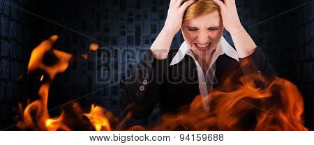 Stressed businesswoman with hands on her head against dark grey room