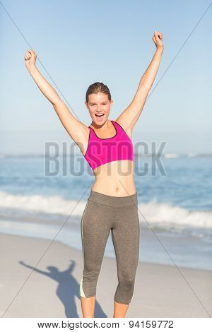 Wear view of beautiful fit woman cheering with arms rise at the beach