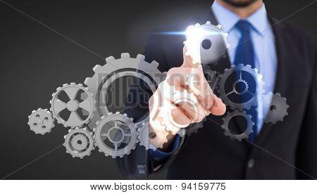Businessman pointing his finger at camera against grey vignette