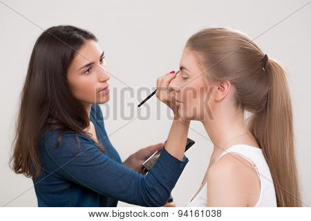 make-up artist doing make-up of a beautiful young girl