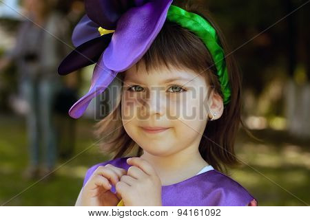The Little Girl In A Suit Of Violet Flower Is Smiling On The Background Of The Park. Close Up Portra