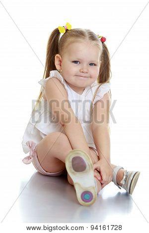 Beautiful little girl sitting on the floor