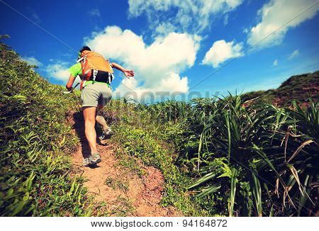 young woman backpacker climbing on seaside mountain trail