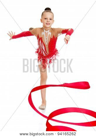 Young gymnast performs exercises with the tape