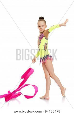 Slender girl gymnast performs exercises with the tape