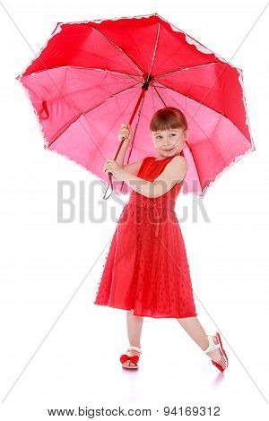 Portrait in red, adorable little girl holding an umbrella